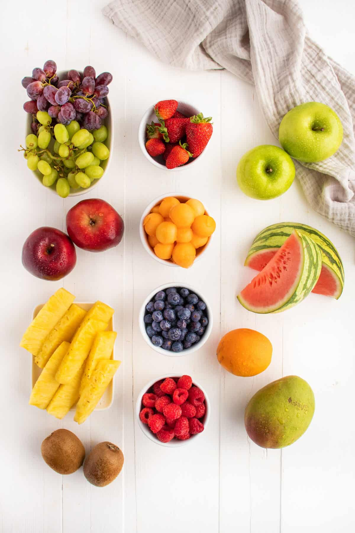 types of fruit for a fruit platter, raspberries, blueberries, grapes, apples, watermelon, oranges, mangoes, pineapple and kiwis