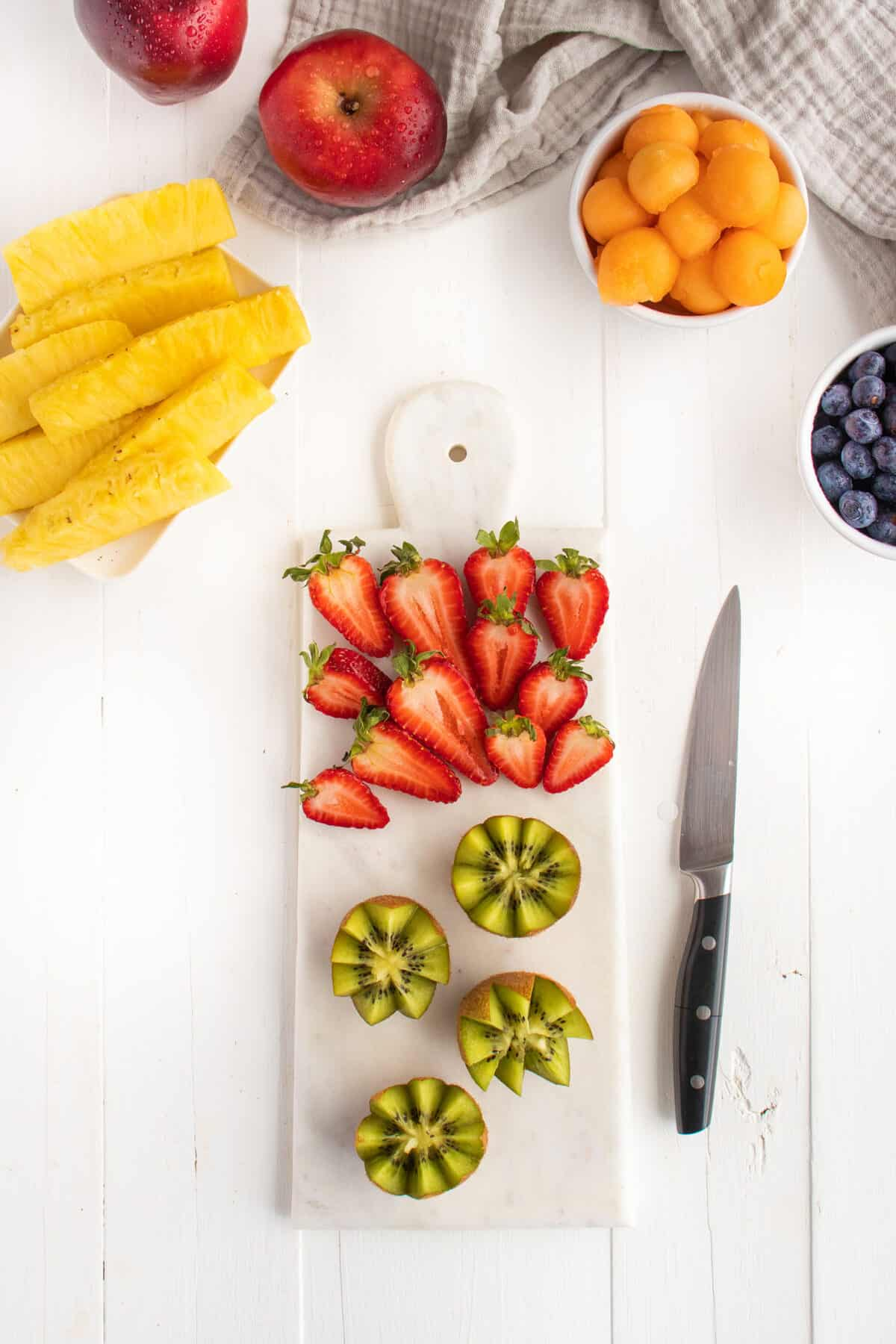 strawberries and kiwis with a knife on a white board