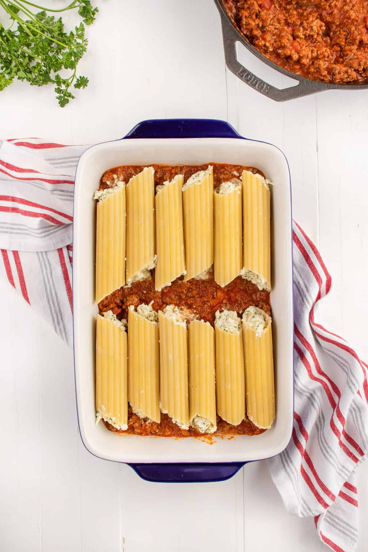 filling manicotti pasta and placing them into the baking pan