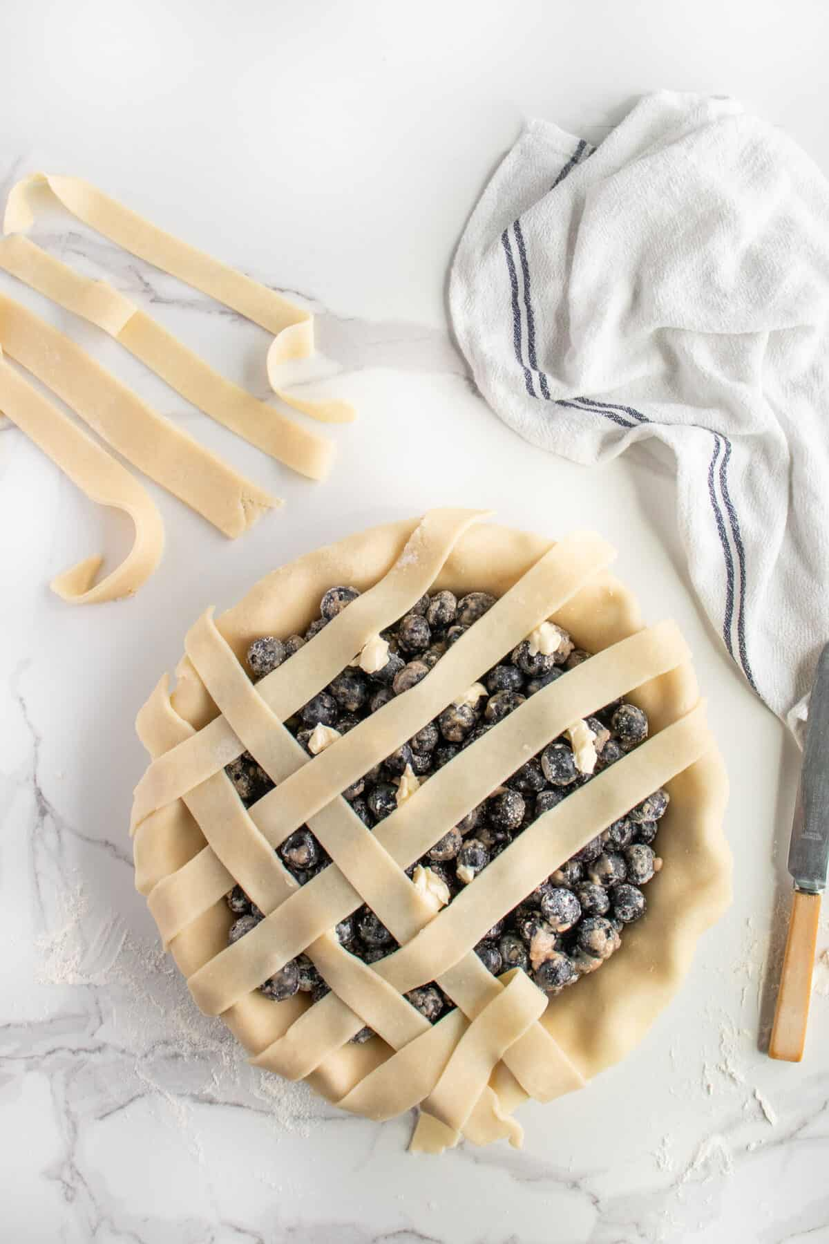 placing pie crust in a lattice pattern on top of blueberry pie