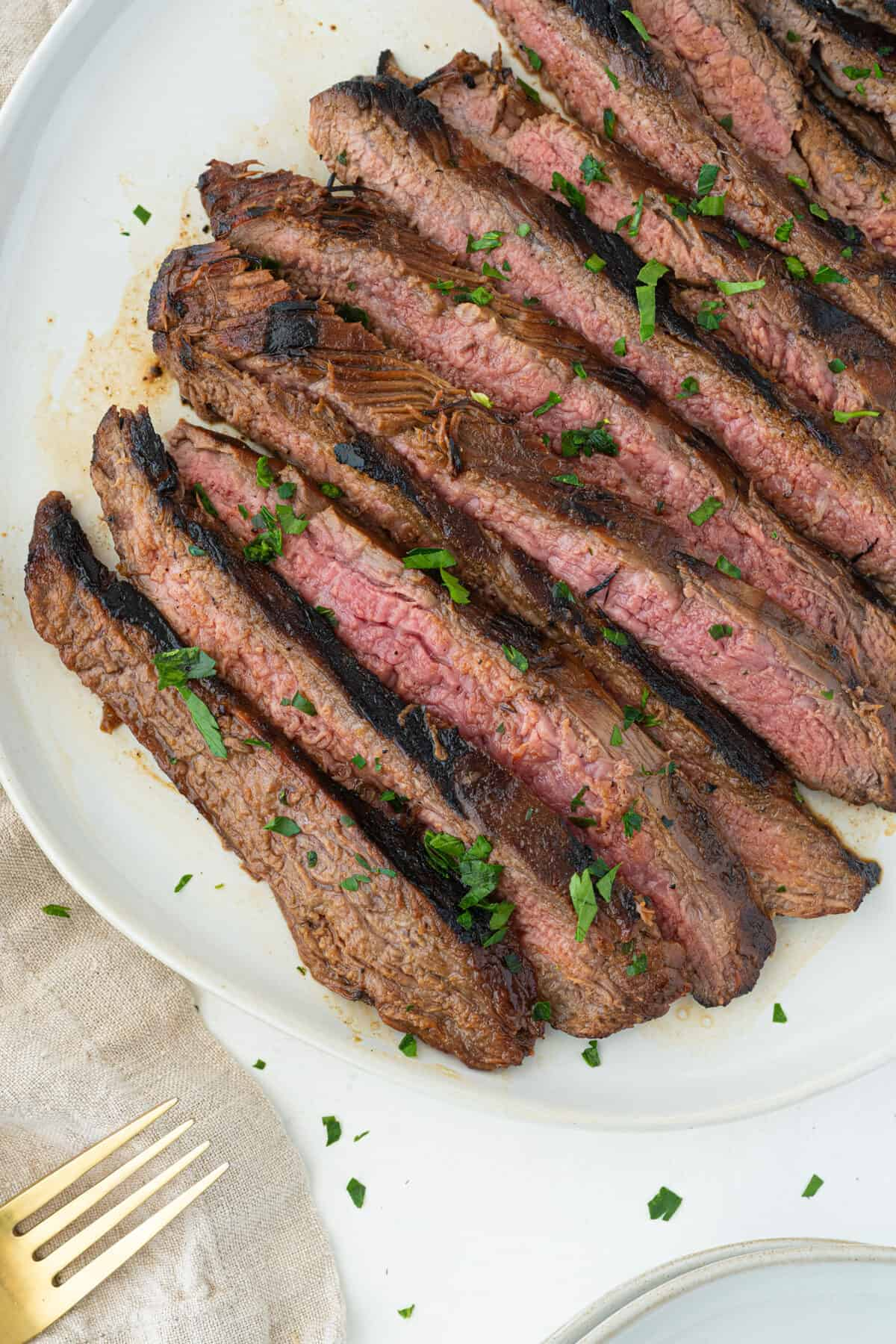 Sliced and cooked marinated flank steak on a white plate