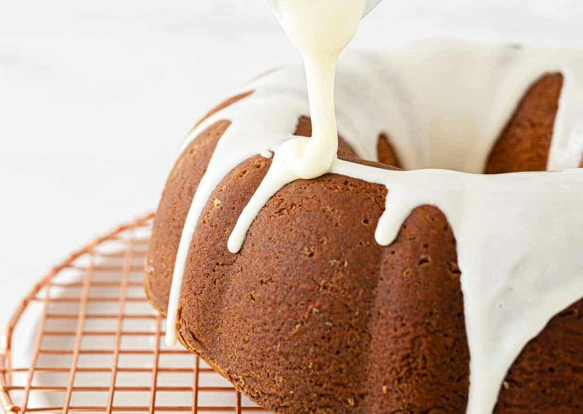 drizzling powdered sugar glaze on a cake