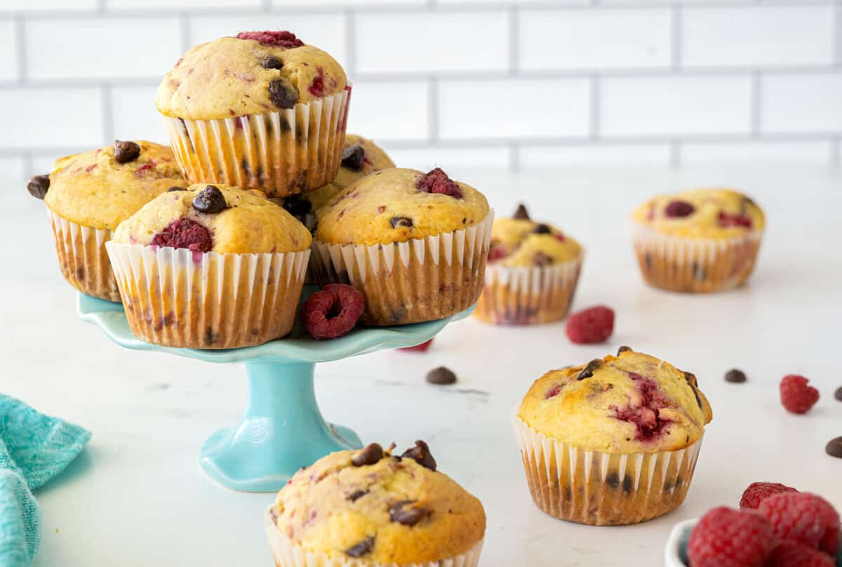 A group of raspberry muffins on top of a serving plate, with other muffins, raspberries and chocolate chips scattered nearby.