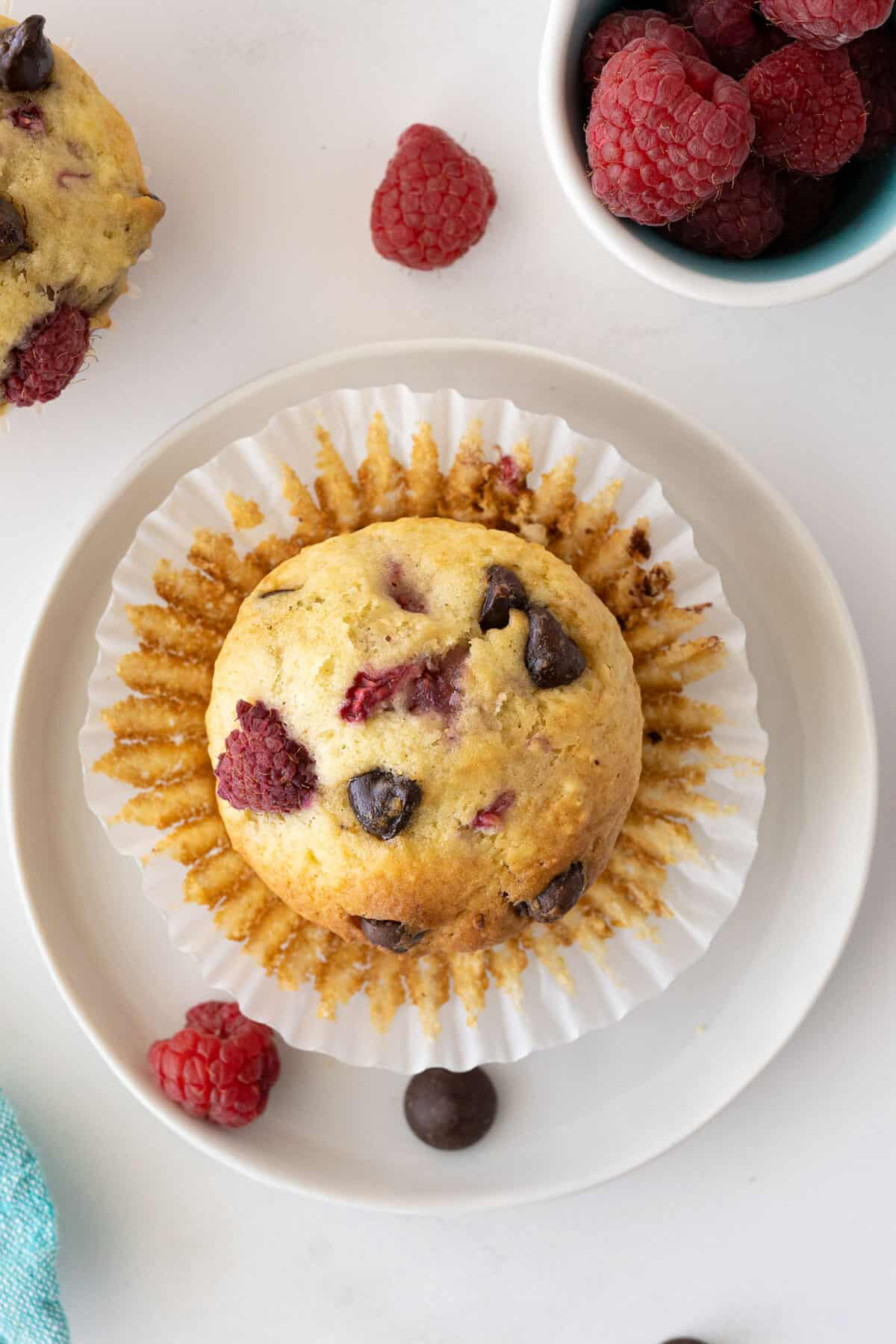 A freshly cooked raspberry muffin, its wrapped peeled back, on a white plate.