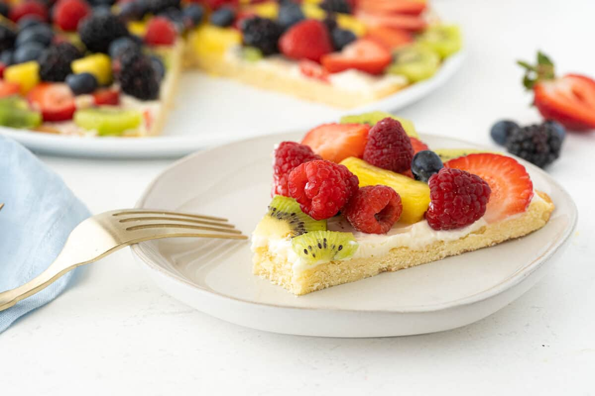 slice of fruit pizza on a white plate with a fork beside it