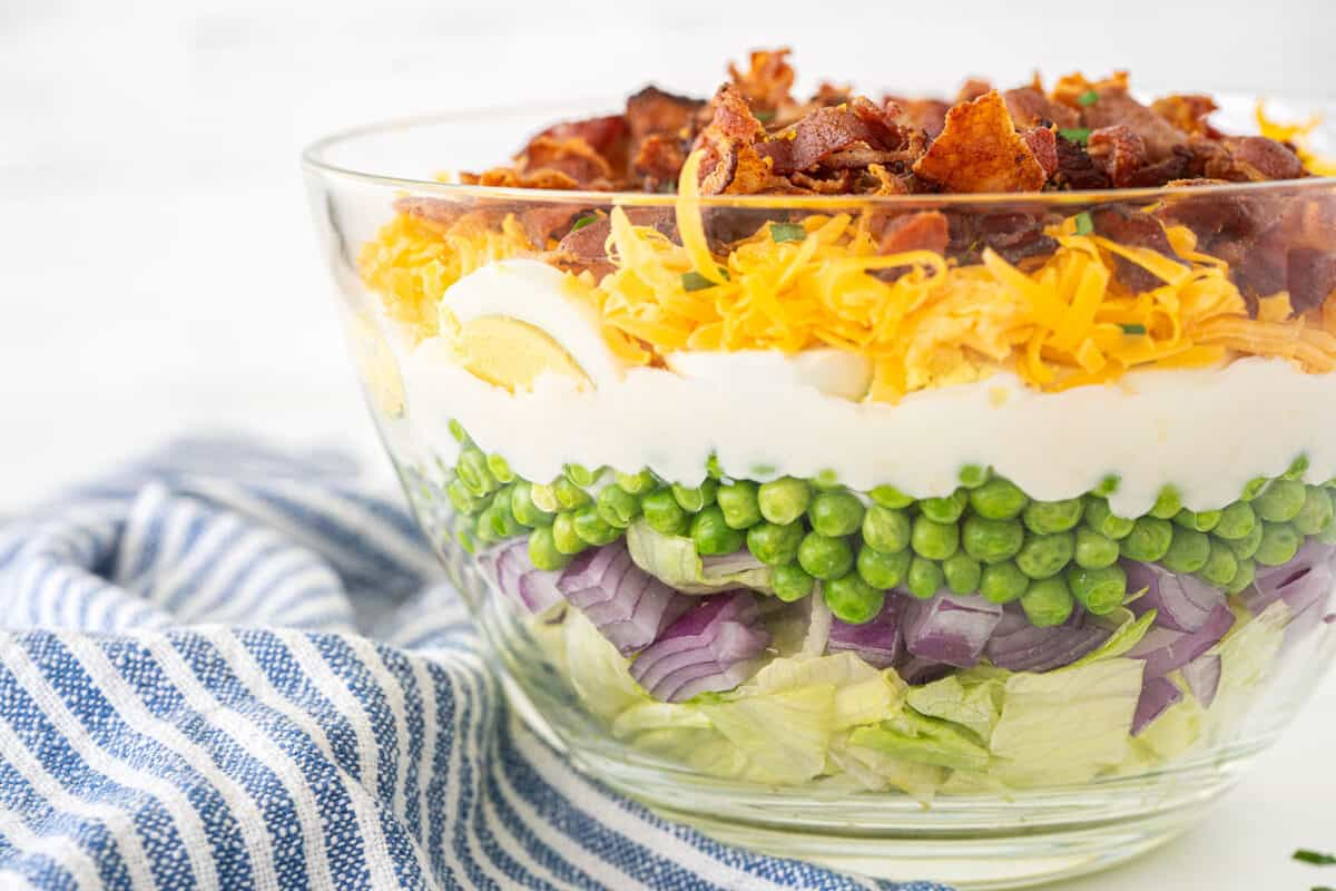 7 layer salad in a clear bowl