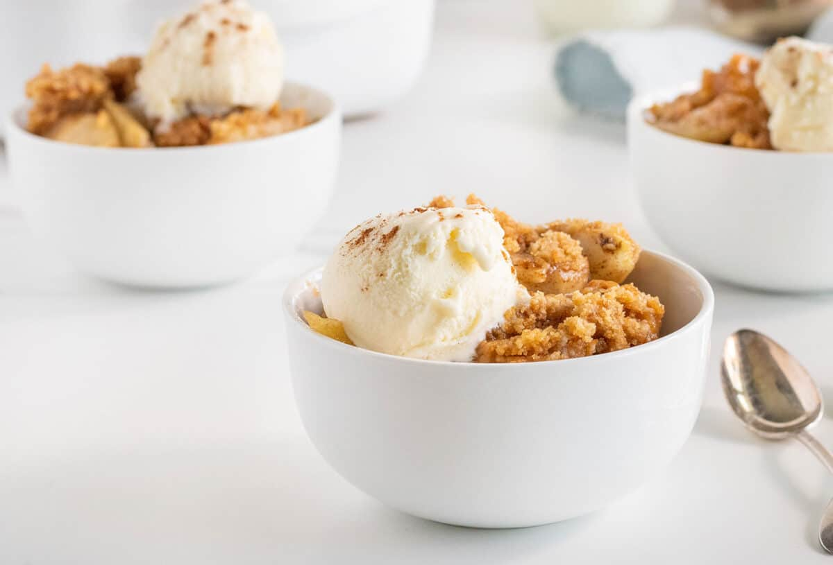 Apple Brown Betty in a white bowl with vanilla ice cream on top