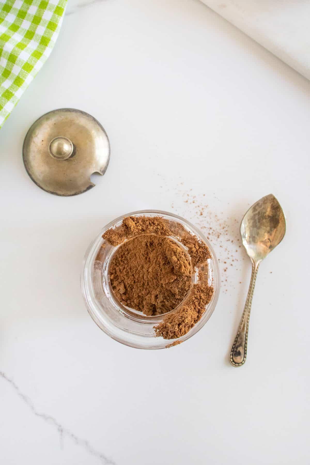 adding apple pie spice to a glass jar