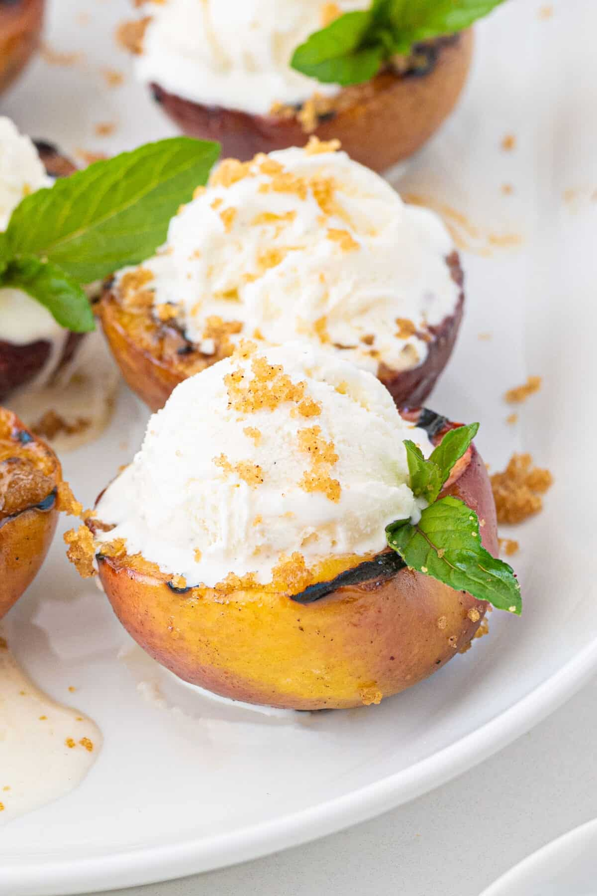 grilled peaches topped with vanilla ice cream and crumbly topping