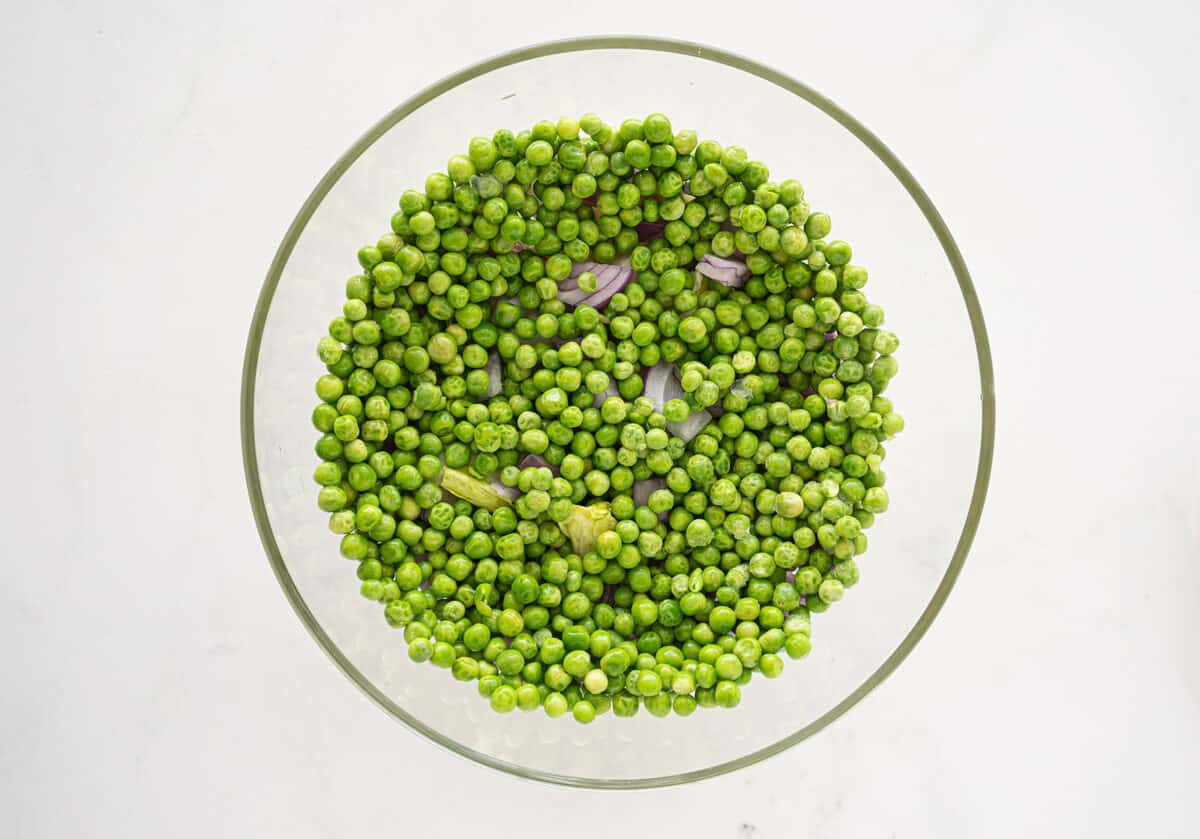 peas on top of onions in a bowl