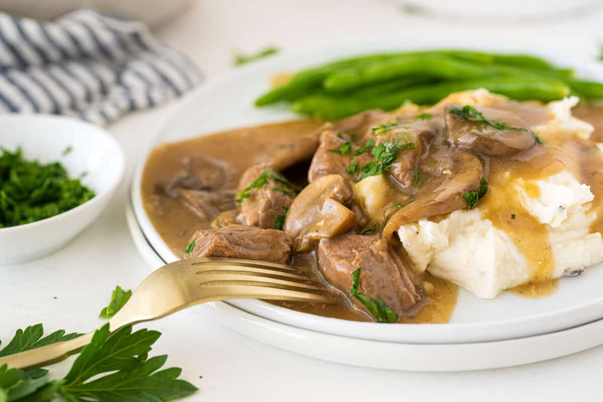 beef tips and gravy served over mashed potatoes  on a white plate
