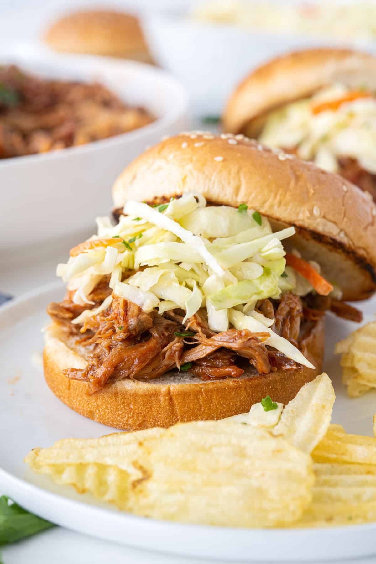 close up of a pulled pork sandwich on a white plate