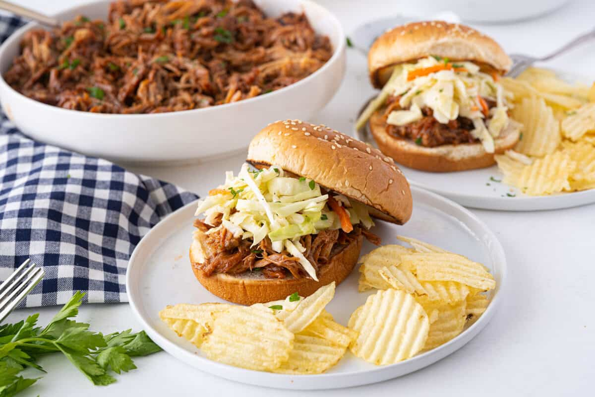 pulled pork sandwiches on a white plate with potato chips