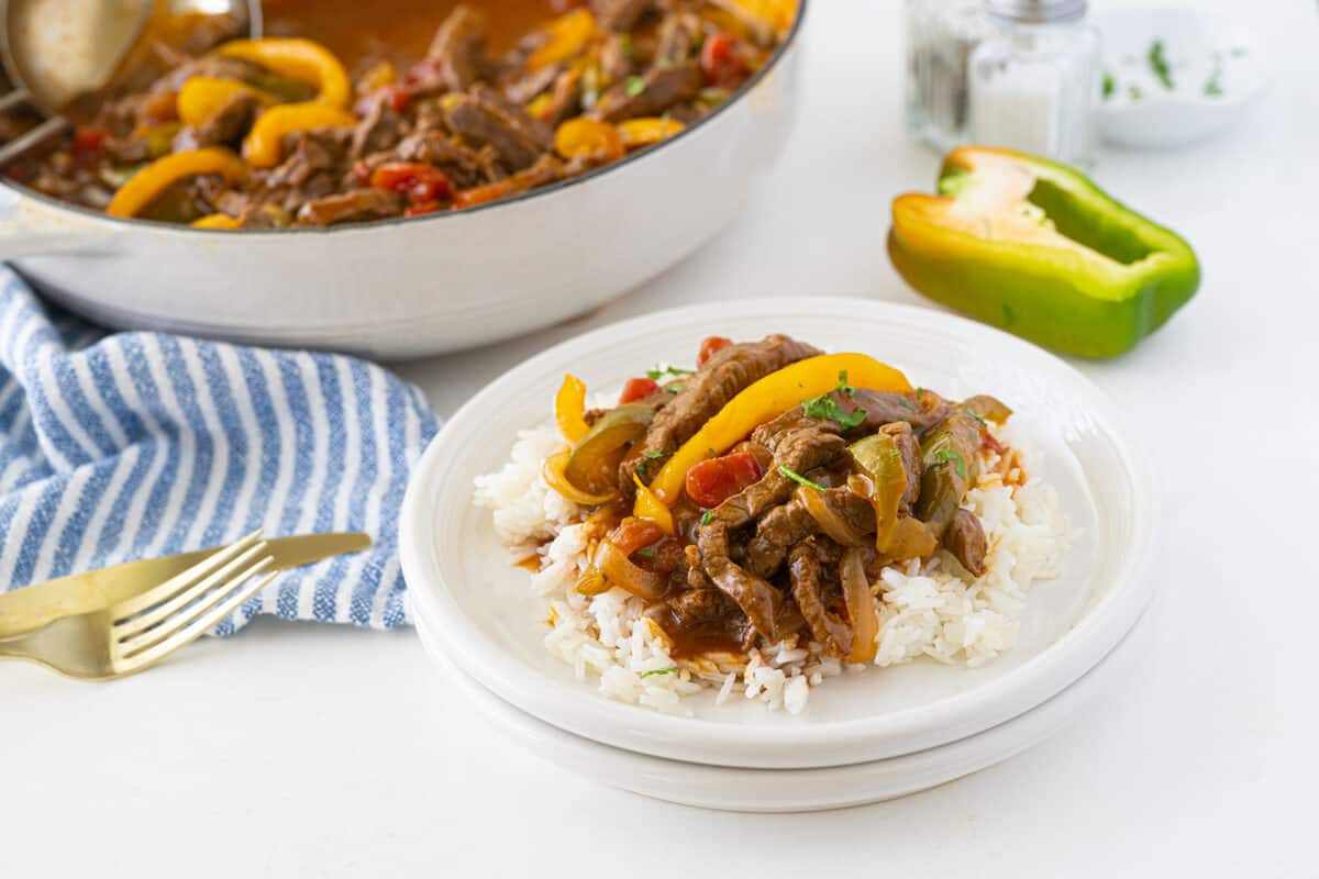 pepper steak on rice on a white plate