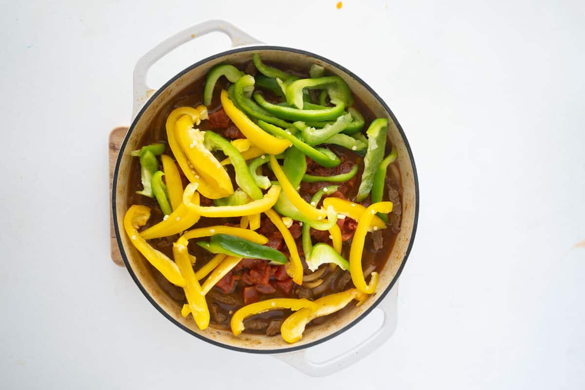 green and yellow peppers in a braising pan