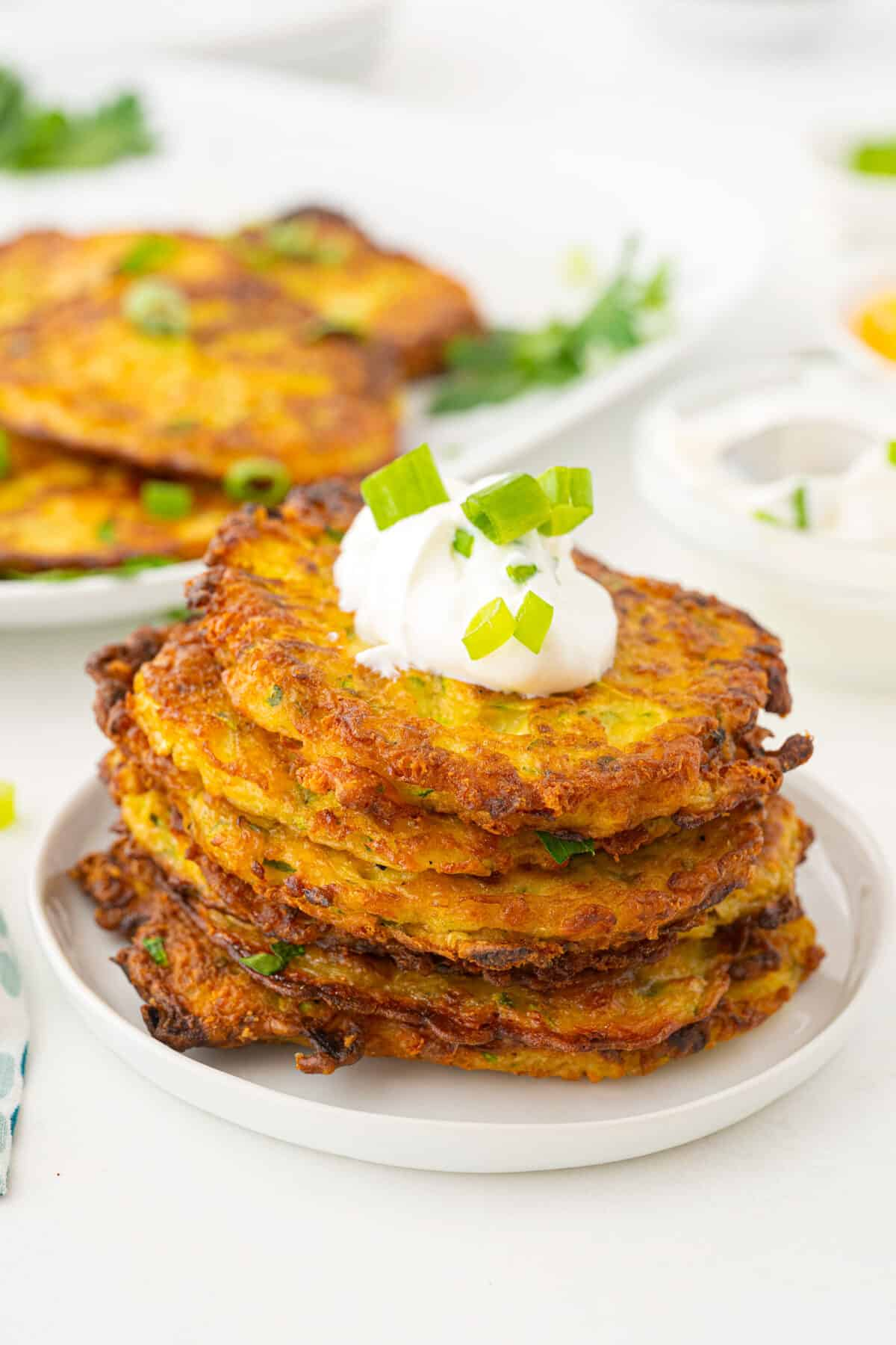 a pile of zucchini fritters on a plate with sour cream and green onions on top